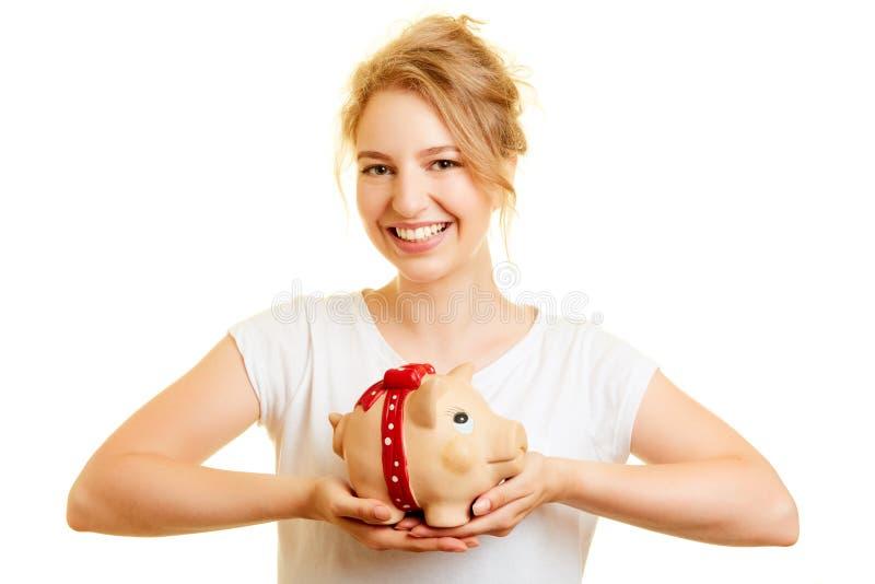 年轻女人拿着存钱罐作为财务概念 图库摄影