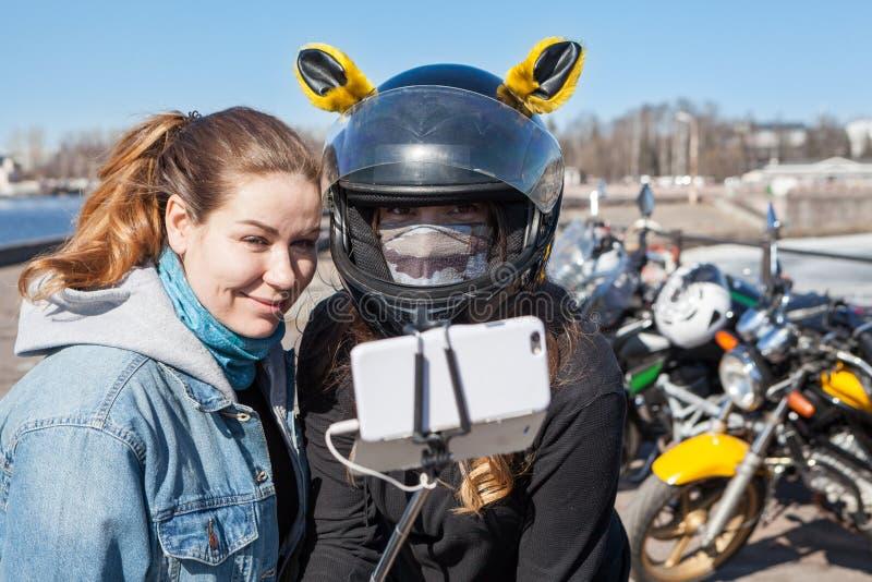 年轻女人摩托车骑士采取selfies使用有延伸性monopod的手机 图库摄影