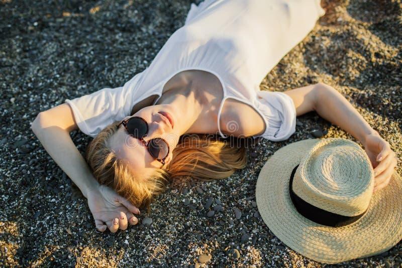 年轻女人放松,在沙子在海滩 图库摄影