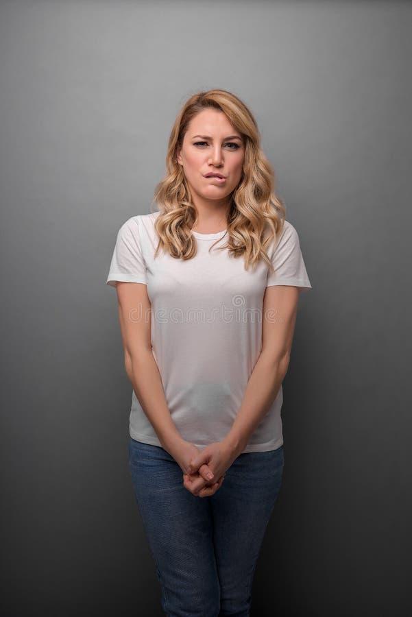 年轻女人斜眼看一副酸鬼脸,当站立反对灰色背景时 库存照片