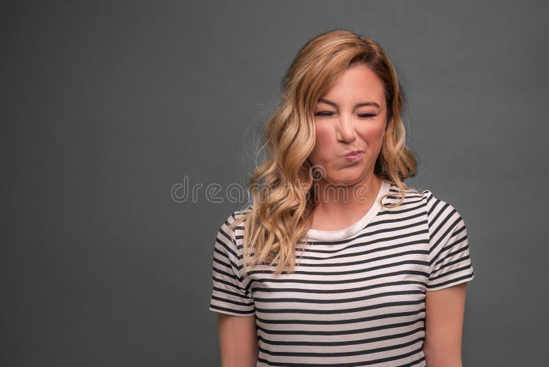 年轻女人斜眼看一副酸鬼脸,当站立反对灰色背景时 免版税库存图片