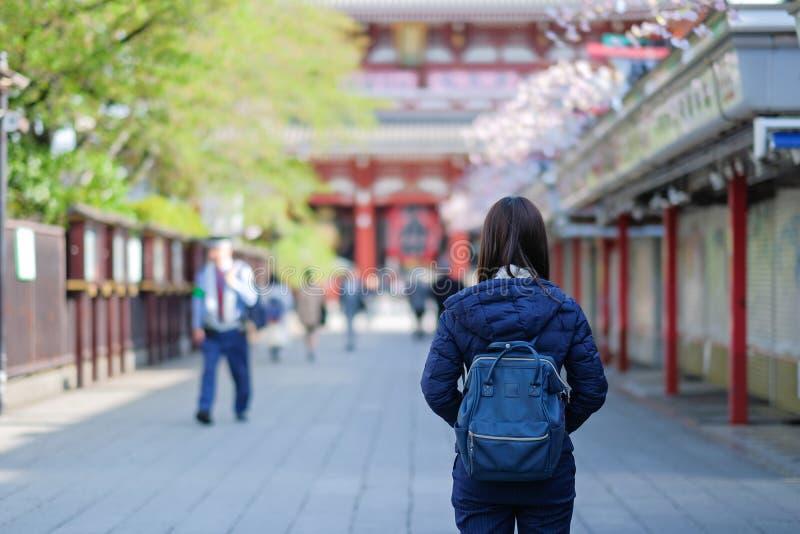 年轻女人旅行的背包徒步旅行者、亚洲旅客身分在Sensoji或浅草Kannon寺庙 地标和普遍游人的在 库存照片