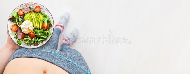 年轻女人是休息和吃健康食品在锻炼以后 免版税图库摄影