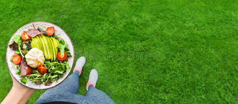 年轻女人是休息和吃健康食品在锻炼以后 库存图片