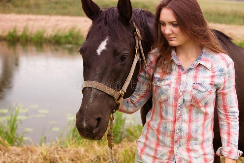 年轻女人有她的黑马的身分户外 免版税图库摄影