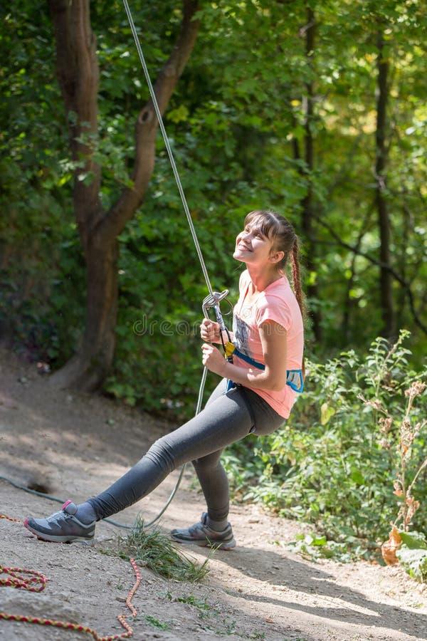 年轻女人有安全绳索的攀岩运动员照片在绿色树背景的手上  免版税图库摄影