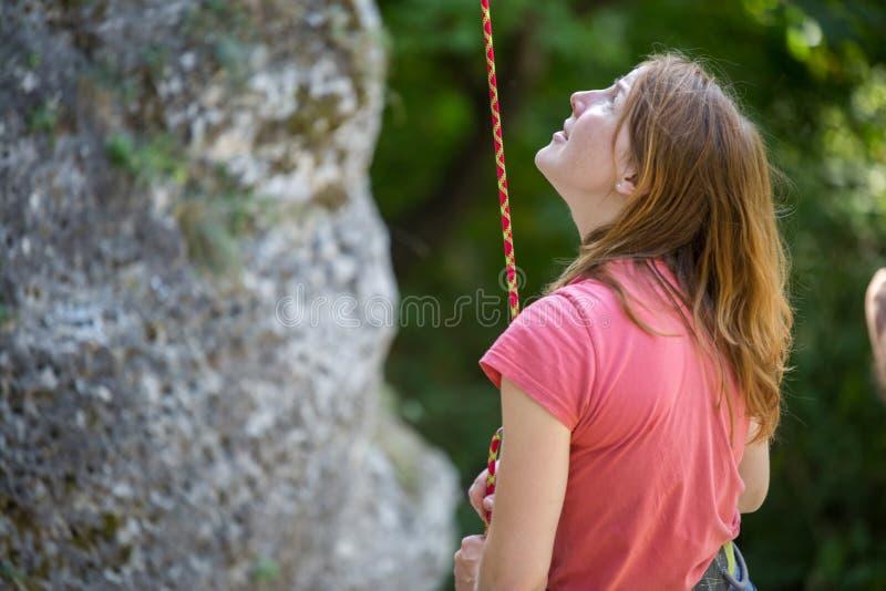 年轻女人有安全绳索的攀岩运动员的图象在岩石的手上在绿色树背景的  免版税图库摄影