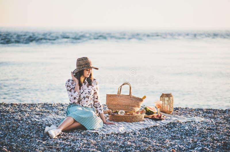 年轻女人有野餐在日落在海边用开胃菜 库存图片