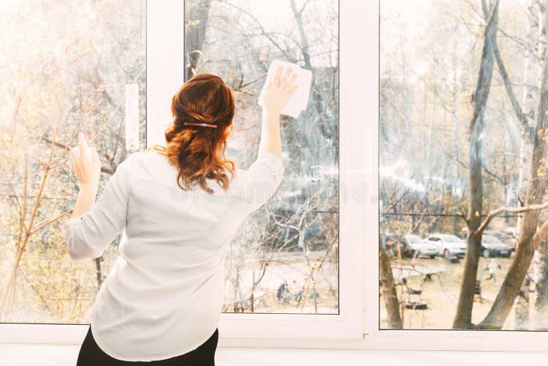 年轻女人洗涤的窗口 免版税库存照片