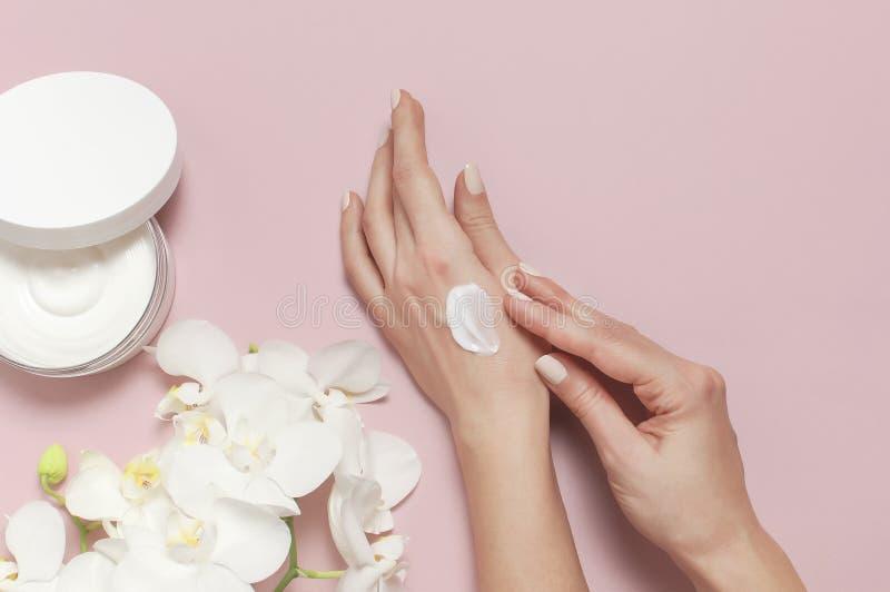 年轻女人润湿她的有化妆奶油色化妆水的手有奶油色身体乳白色的兰花植物兰花的打开容器 库存照片