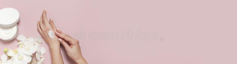 年轻女人润湿她的有化妆奶油色化妆水的手有奶油色身体乳白色的兰花植物兰花的打开容器 免版税库存照片