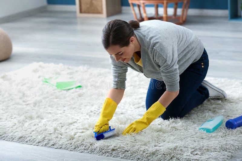 年轻女人清洗的地毯在家 库存照片