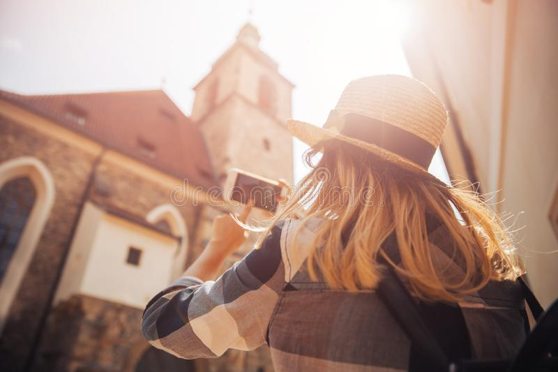 年轻女人游人草帽的和有背包的使用电话作为照相机,为大厦照相 库存图片