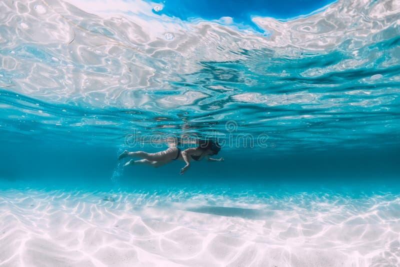 年轻女人游泳的水中在有沙子的热带蓝色海洋 库存照片