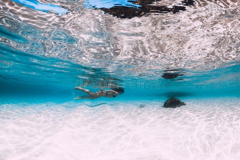 年轻女人游泳的水中在有沙子的热带蓝色海洋 图库摄影