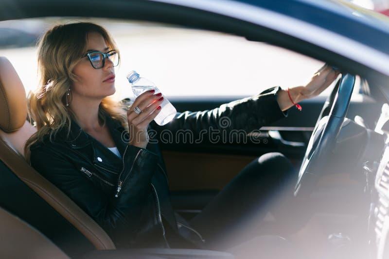 年轻女人照片有瓶的水在她的坐在汽车的手上 库存图片