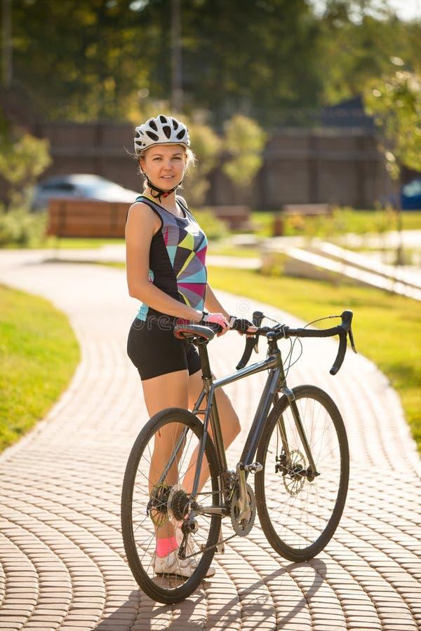 年轻女人照片盔甲的在自行车乘驾在夏日 免版税图库摄影