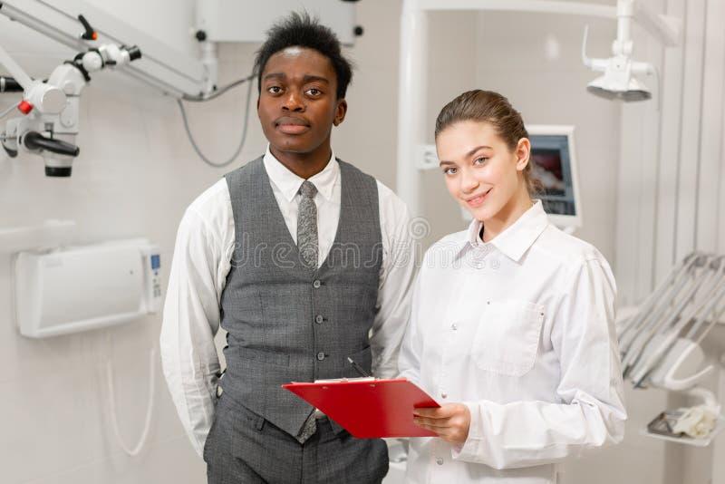 年轻女人牙医提出一个诊断和纪录建议 牙齿诊所的非洲男性患者 ?? 免版税库存图片