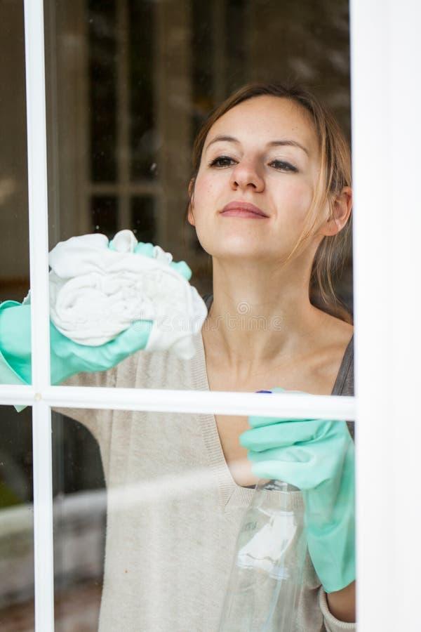 年轻女人用海绵擦窗 库存照片