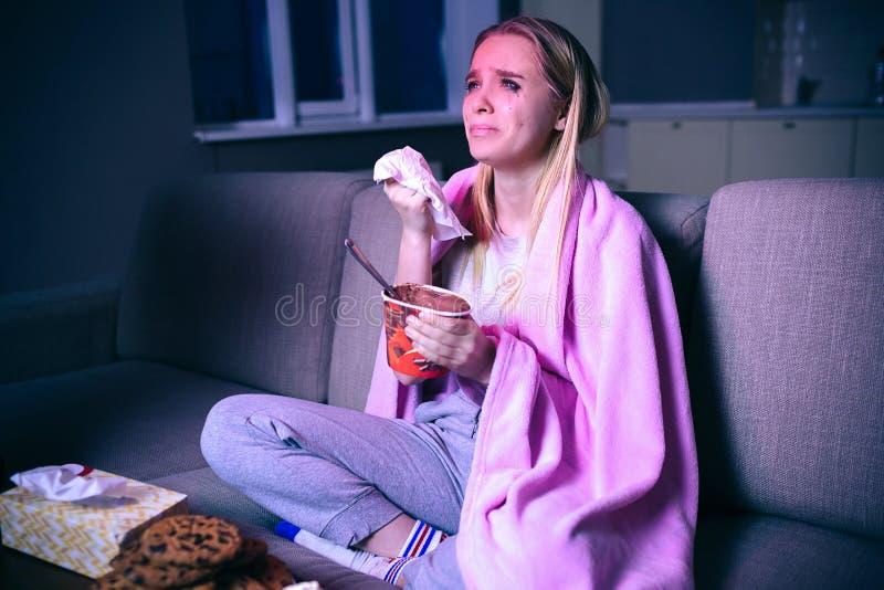 年轻女人电影在晚上 坐沙发和哭泣 放出展示或电视剧的观看的哀伤的电影 ? 免版税库存照片