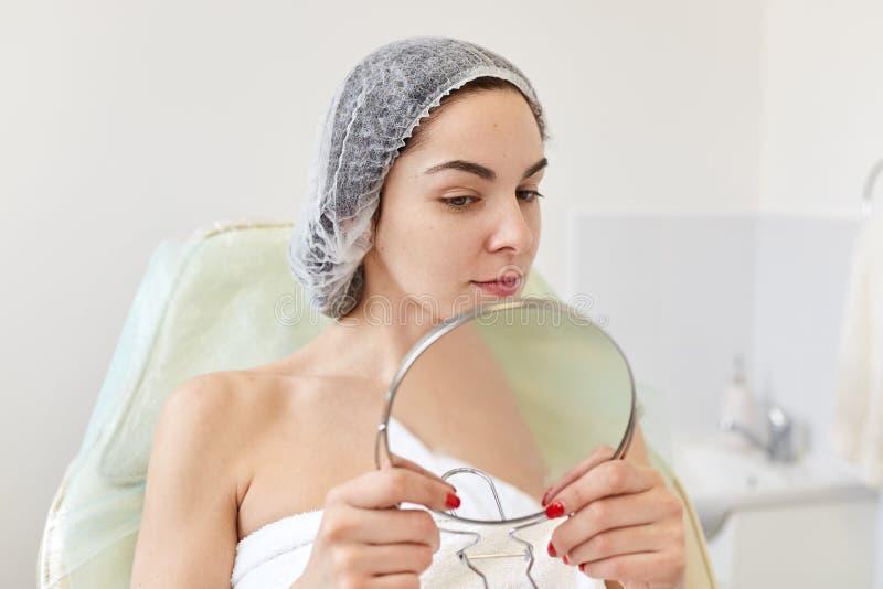 年轻女人画象在cosmetological做法以后的在诊所 可爱的女性在手和神色上拿着镜子在结果  库存照片