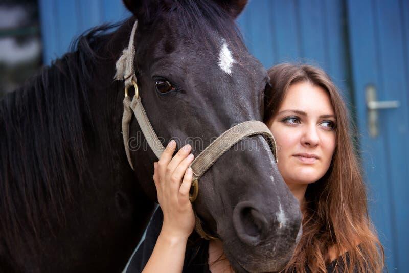 年轻女人画象有她的黑马的 免版税库存图片