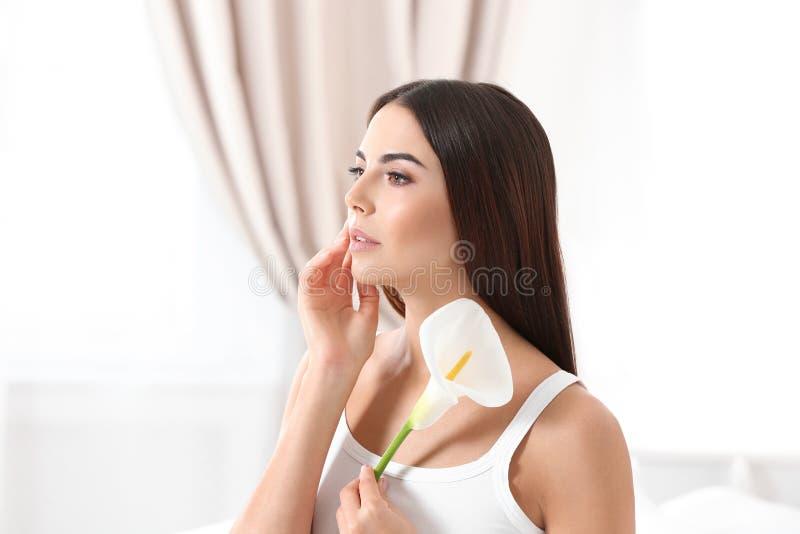 年轻女人画象有水芋属花的 r 免版税库存照片