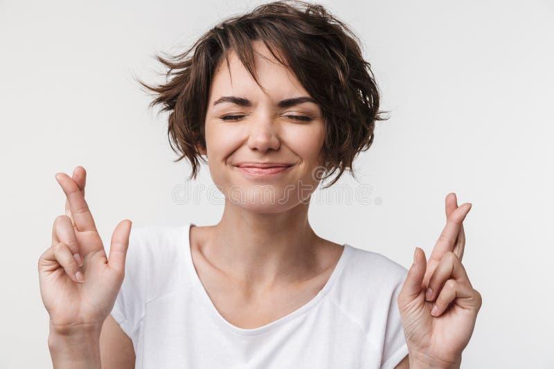 年轻女人画象有短的棕色头发的在保持但愿和祝愿好运的基本的T恤杉 免版税库存照片