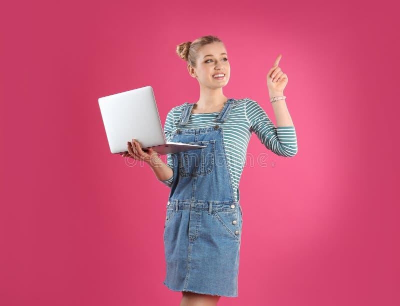 年轻女人画象有膝上型计算机的在桃红色 免版税库存图片