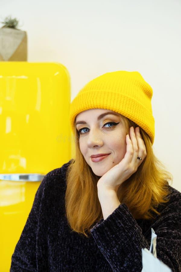 年轻女人画象有金发的在一个黄色帽子在咖啡馆坐近染黄冰箱 免版税库存照片