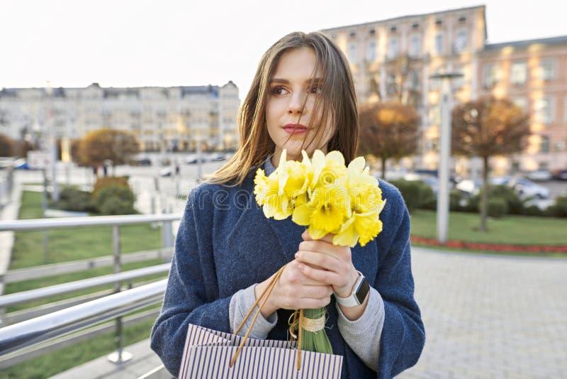 年轻女人画象有黄色春天花黄水仙花束的  美女关闭,春天城市背景 免版税库存照片
