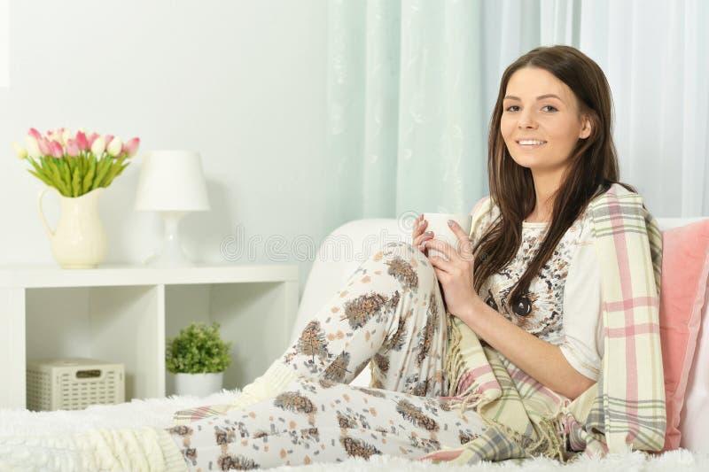 年轻女人画象睡衣的在与蓬松格子花呢披肩的床上 库存照片