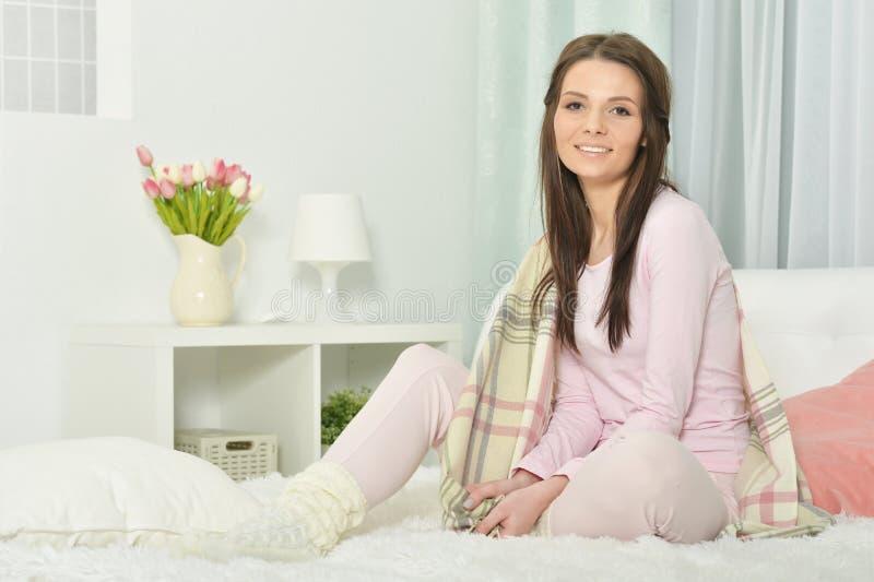 年轻女人画象睡衣的在与蓬松格子花呢披肩的床上 库存图片