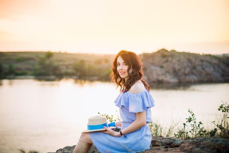 年轻女人画象蓝色浪漫礼服的有坐在河附近和享受日落晚上的帽子的 r ?? 免版税库存图片