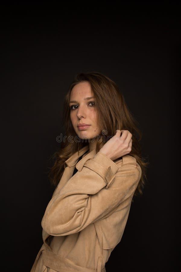 年轻女人画象黑顶面和米黄军用防水短大衣的在黑背景 免版税库存图片