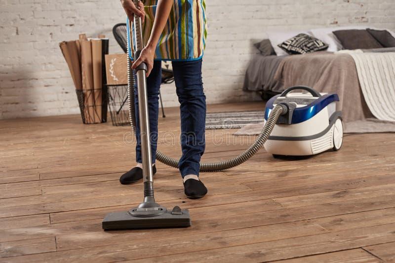年轻女人的匿名的中段使用吸尘器的在家庭客厅地板,做清洗的责任和差事 库存照片