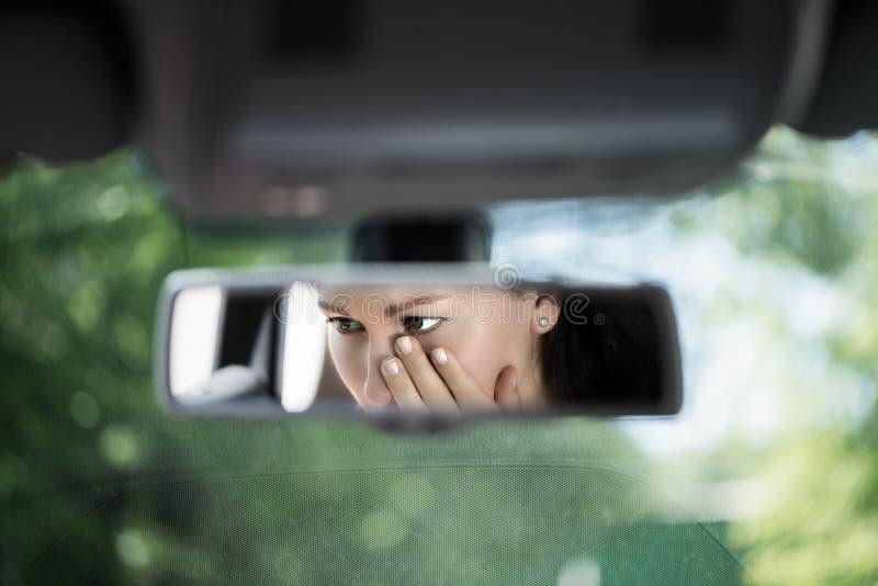 年轻女人的反射有盖她的面孔的哭泣的眼睛的用在汽车后视镜的手 事故的概念 免版税库存照片