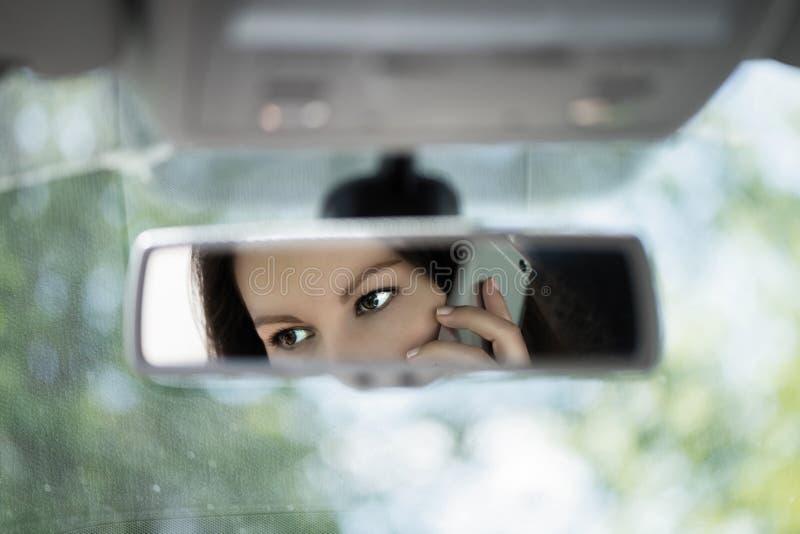 年轻女人的反射谈话在汽车后视镜的一个手机 没有手机,当驾驶时 免版税库存图片