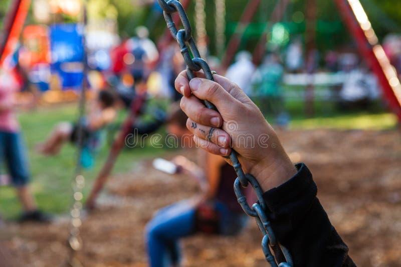 年轻女人的手的特写镜头图片拿着摇摆链子的在公园 免版税图库摄影