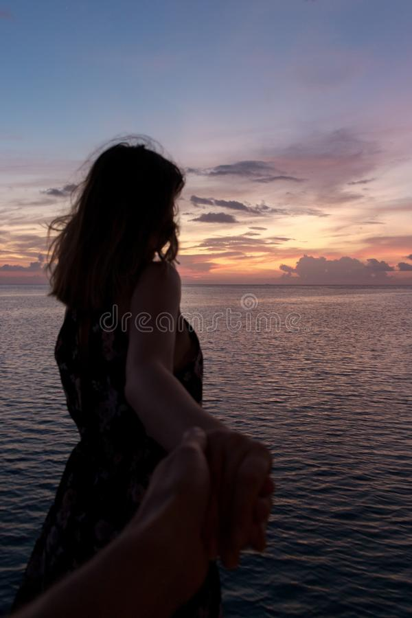 年轻女人的跟我学概念看日落的海滩的 图库摄影