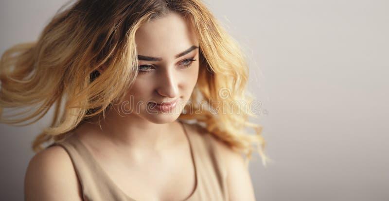年轻女人的软的演播室画象,与从风弄乱的卷发的女孩面孔,自然美人的概念, 免版税库存照片