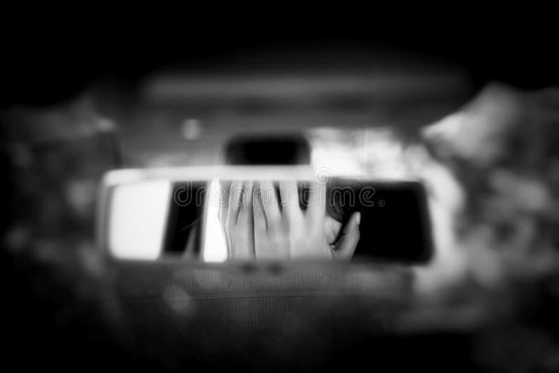 年轻女人的黑白艺术图片有盖她的面孔的害怕眼睛的用在汽车后视镜的手 库存照片