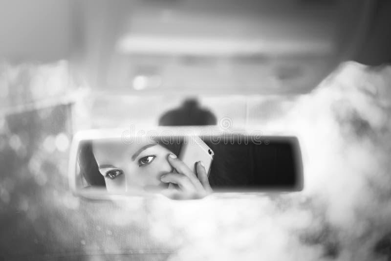 年轻女人的黑白艺术图片谈话在汽车后视镜的一个手机 库存图片