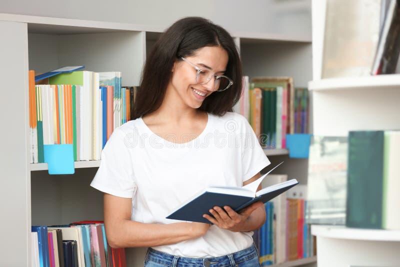 年轻女人看书在图书馆里 免版税图库摄影