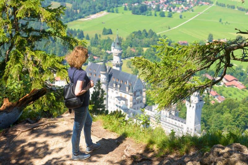 年轻女人看着德国巴伐利亚新天鹅堡 图库摄影