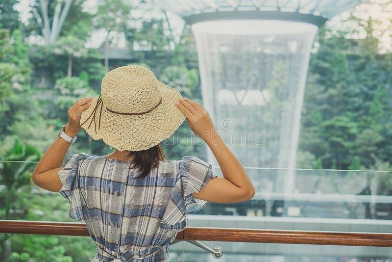 年轻女人穿戴蓝色礼服和帽子,亚洲旅客身分和看对美好的雨漩涡珠宝樟宜机场, 库存照片