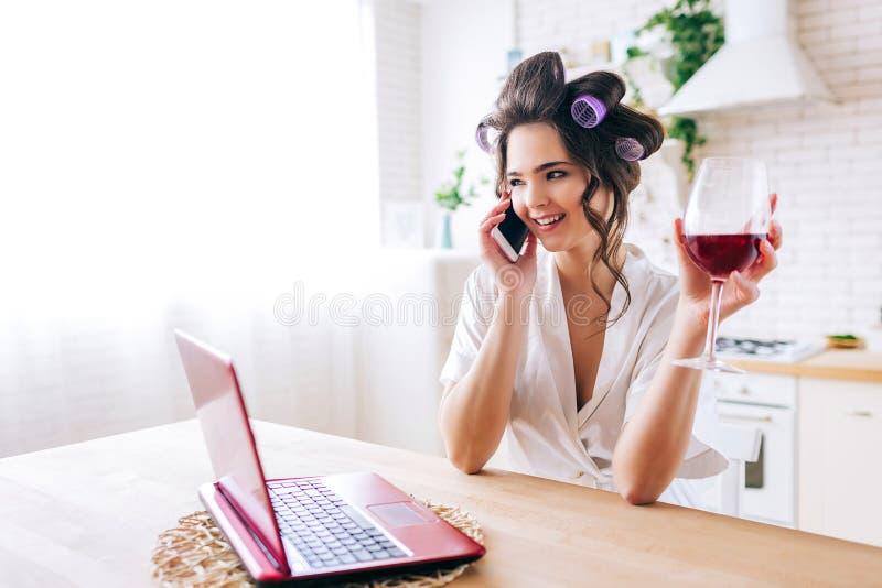 年轻女人立场在厨房里和谈话在电话 拿着在手中红酒酒杯 有卷发的人的管家在头发 免版税库存图片