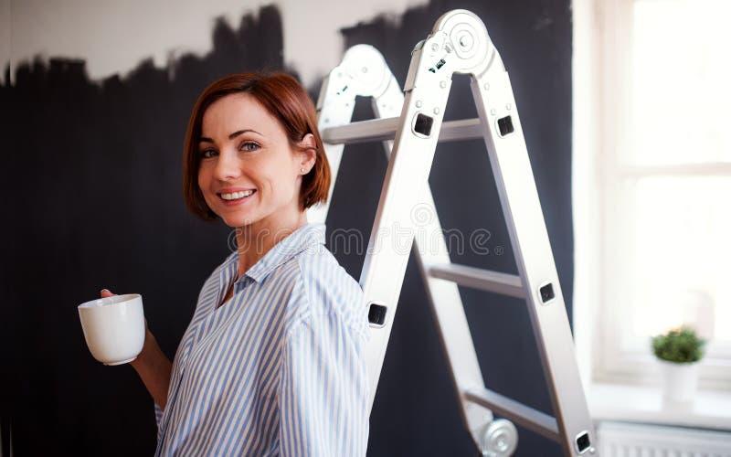 年轻女人绘画墙壁黑色画象  小企业起动  库存照片