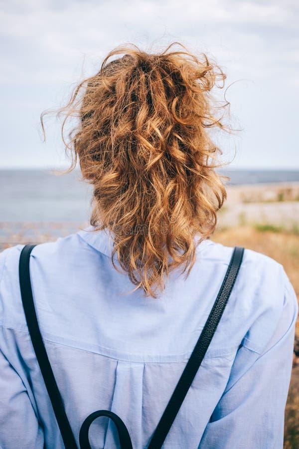 年轻女人背面图有厚实的卷发的 免版税库存图片