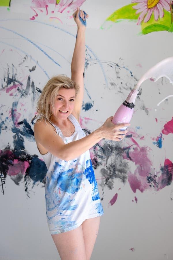 年轻女人艺术家打开一个闪耀的瓶在有颜色被弄脏的白色的汗衫的香槟生日宴会 库存照片